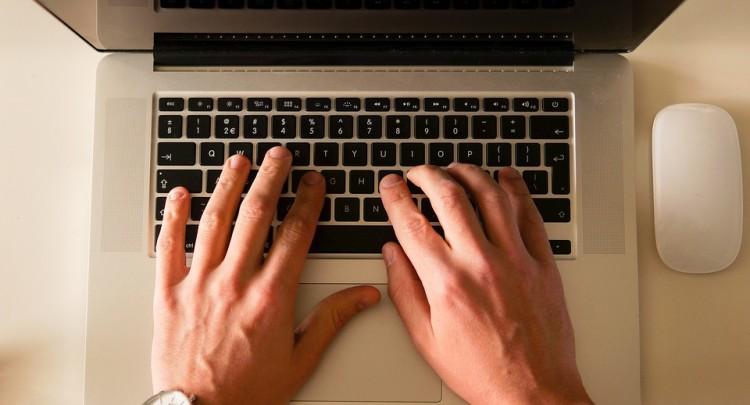 Bureau avec un MAC, ordinateur portable et des mains